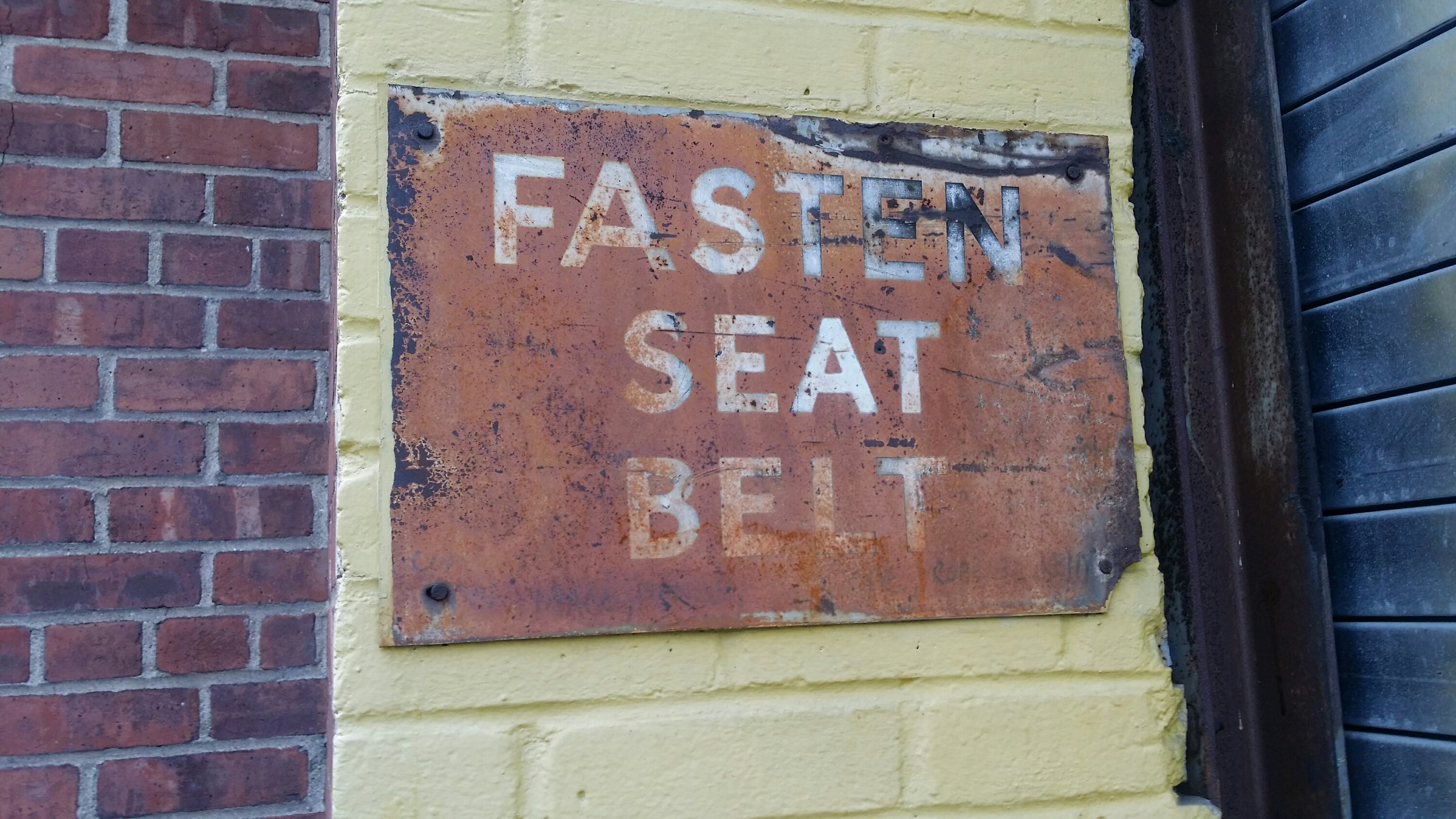 Fasten seat belt vintage hand panted sign rust metal old